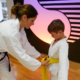 Kinder Kampfkunst Frau bindet Kind den neuen Gürtel