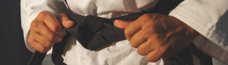 Mann bindet seinen Schwarzen Gürtel